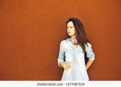 Beautiful modern young girl in headphones with a phone stands near the orange wall. The concept of urban style, youth and trends, feminism, emancipation, women's rights