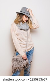 Beautiful modern young woman in autumn casual outfit. Studio portrait of gorgeous blonde teenage girl in neutral toned clothes and accessories.