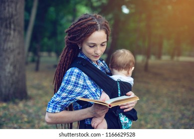 Beautiful mom with a baby in ergo backpack reading a fairy tale in the Park. Children's education in family life