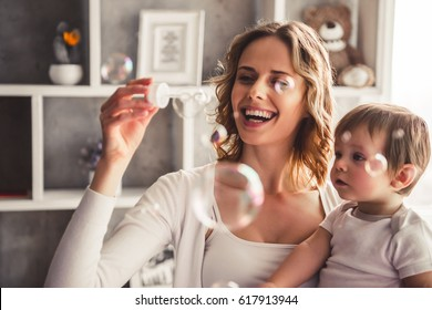 Beautiful mom is blowing soap bubbles while playing with her cute baby boy at home and smiling
