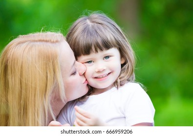 Beautiful mom and daughter, has happy fun smiling face, pretty eyes, blonde and haired hair, pure skin make up, dressed in white t-shirt. Family portrait. Close up. Love concept. Summertime.
