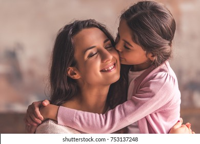 Beautiful mom and daughter are hugging, mom is smiling while girl is kissing her in cheek