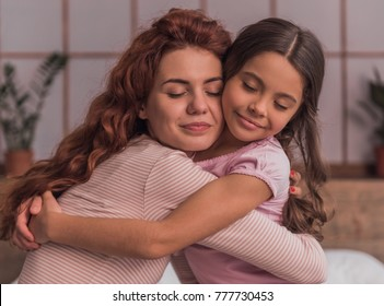 Beautiful mom and her cute daughter are hugging and smiling while spending time together at home