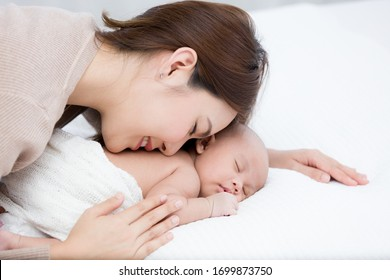 Beautiful mom supports and tenderly cuddles the newborn baby gently while the infant is sleeping on the white bed. Asian mother kissing and touching on the back of babies with love and care.