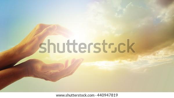 Schöner Moment in der Natur - weibliche Hände mit abendlichem Sonnenlicht gefangen zwischen und schönen sanften Dämmerwolken auf Hintergrund