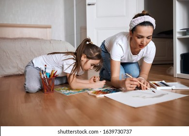 beautiful mommy and her kid paintig a picture for kindergardern. hobby, education, development , child developing painting skills. close up photo