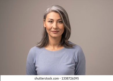 Beautiful Mongolian Woman with Gray Hair on a Gray Background. Woman's Face Has a Relaxed Smile. She is Wearing a Soft Blue Blouse. Close Up Shoot.