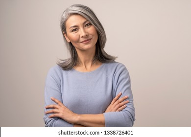 Beautiful Mongolian Woman with Gray Hair on a White Background. Arms Crossed She Gently Smiles. Her Gaze Looks Contented. Mongolian Beauty Concept. Close Up Shoot.