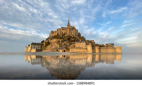 Beautiful Mont Saint Michel with water reflection and clouds on blue sky, France