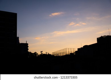 Beautiful moody colorful sunrise creates a city silhouette over the rooftops in a small town in Japan