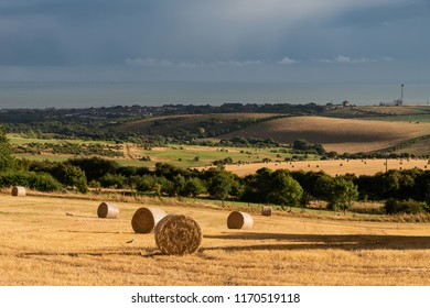 Beautiful moody Summer landscape of field of hay bales with dramatic stormy clouds overhead in English countryside