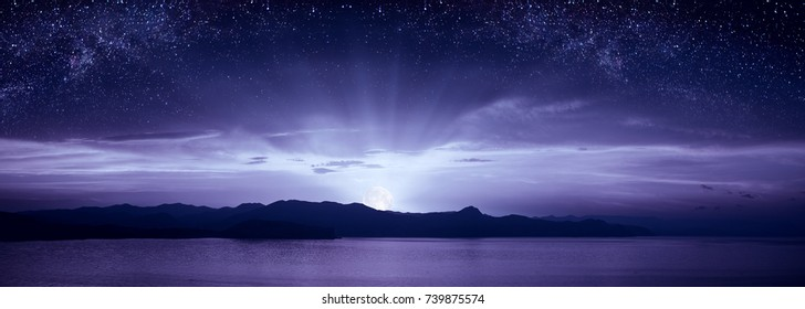 Beautiful moonrise over the sea. Milky way in a starry sky. Night landscape. Panoramic format.