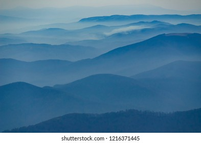 Beautiful morning alpine landscape with tonal perspective. Blue tonality mountains with foggy valleys look like sea waves