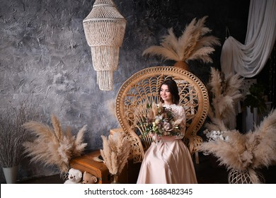 Beautiful morning bride in boho style. Bride brunette in a cream dress with a wedding bouquet in her hands sits on a straw armchair. Blue-gray background. Spikelets, feathers and roses.