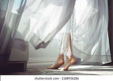 A beautiful morning of the bride.  The bride opens the window.  In the photo naked female legs.  The wind develops curtains.