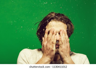 beautiful morning. guy washing face with water drops in morning. man with long hair refreshing in underwear on green background, hygiene and skincare, health and wakeup, everyday life, barbershop