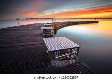 Beautiful morning at the lake on a long jetty with wooden planks, morning dew and a colorful sunrise.