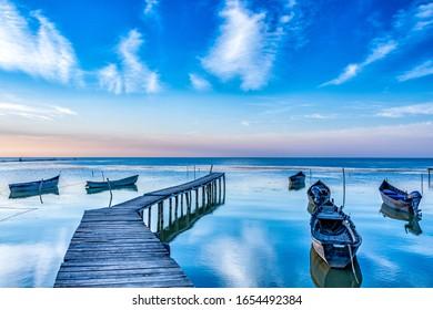 Beautiful morning landscape with boats on the lake anchored to the pier and wood bridges at sunrise, Razelm Razim Lake, Sarichioi, Romania