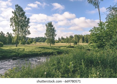 beautiful morning light over forest river of Amata, Cesis, Latvia. sandstone cliffs and green vegetation around water in summer - vintage effect