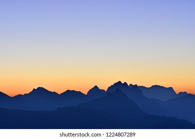 Beautiful morning mood in the Allgaeu Alps at the border region of Germany and Austria. Blue silhouettes of mountain ranges at dawn with orange and blue sky. Zugspitze in the background. Copy space.