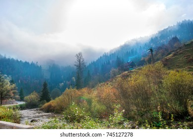 Beautiful morning on highway in mountains. Thick fog around highest mountain tops. Small river with rocks next to road. Colorful and spooky autumn background
