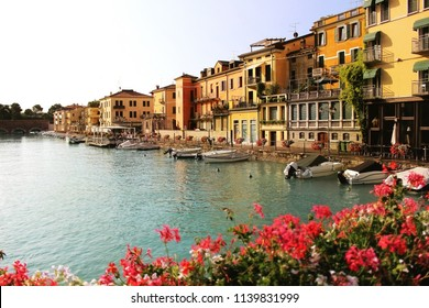 Beautiful morning in Peschiera del Garda town. Colorful houses, architecture view with boats and blurred geranium flowers. Italian lake Lago di Garda, Veneto region of Italy, Europe.