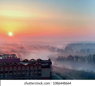 Beautiful morning scenery - calm river, naked trees, fields, school building, courtyard and smoke at the background of colorful sky and rising sun, spring in Moscow region, Razvilka, Russia