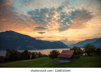 beautiful morning scenery over lake thun and mountains, bernese oberland. swiss alps, rural landscape with hut
