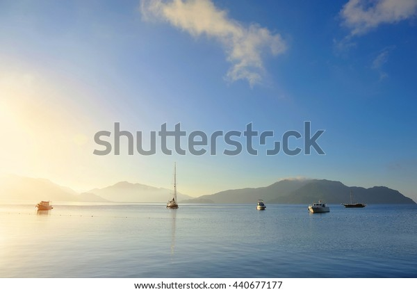 Beautiful morning seascape with boats and mountains in the background