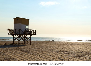 Beautiful morning of summer on the beach. The sun bright over the sea and the lifeguard tower in foreground.