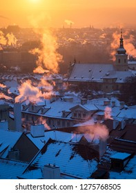 Beautiful morning with sun rising over the Prague roofs covered with fresh snow. Colorful photo of the sunrise in the city.