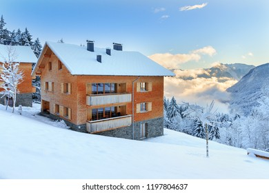 Beautiful morning sunrise view of an apartment building with fresh powder snow in the mountains of the Brandnertal in the Alps in Vorarlberg, Austria, in winter