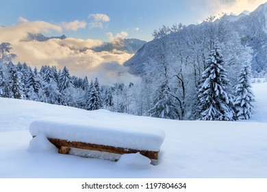 Beautiful morning sunrise view of a bench with fresh powder snow in the mountains of the Brandnertal in the Alps in Vorarlberg, Austria, in winter
