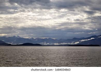 Beautiful morning view of the Mountain Range near Juneau Alaska from the water. Sun breaking through the clouds