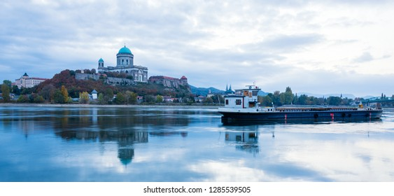 Beautiful morning view on Basilica of the Blessed Virgin Mary and Royal Castle in Esztergom, Hungary with reflection in the water and cargo barge on the Danube River. View from Sturovo, Slovakia.
