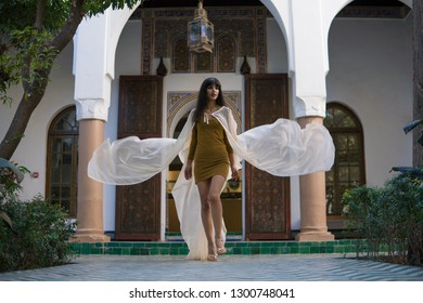 Beautiful Moroccan Girl walking and Waving her white mantle in Rich interior of Picturesque Dar Si Said Riyad in Marrakech