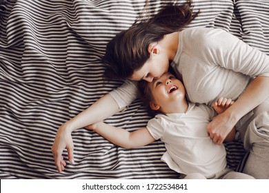 beautiful mother with 3 year old daughter hug and laugh while lying on the striped bed
