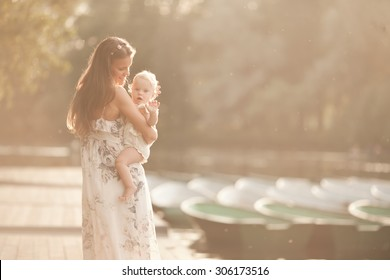 beautiful mother with baby daughter standing on the pier near the lake