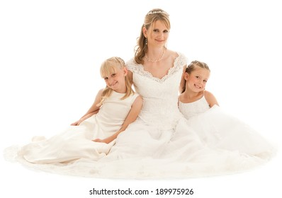 Beautiful mother bride with two young daughters. They all wear white dresses. Studio shot on white background.