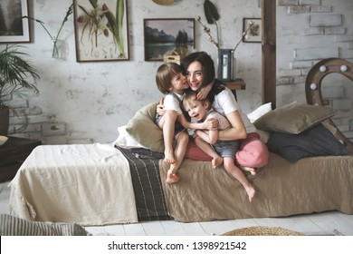 Beautiful mother brunette embraces her sons, brothers boys firmly embrace a tender young mother in a Scandinavian casual gray interior, boys in gray overalls at home