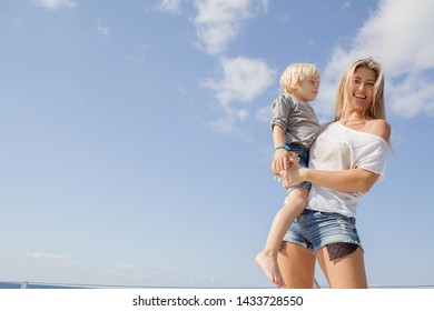 Beautiful mother carrying child boy son on sunny blue sky space, looking smiling outdoors. Family vacation fun activities, leisure recreation lifestyle, bonding healthy holiday summer wellness living.