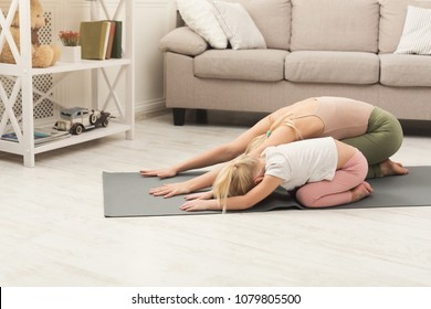 Beautiful mother and charming little daughter are smiling while practicing yoga together at home, making child's pose exercise, copy space