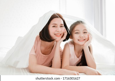 beautiful mother and child girl relaxing and playing in the bed