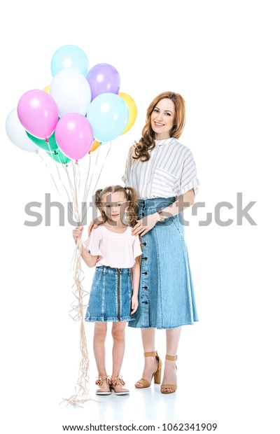 beautiful mother and cute little daughter with colorful balloons smiling at camera isolated on white