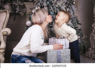 beautiful mother and cute son sitting on the floor near the christmas tree and decorations holding and playing with present boxes. mom going to kiss child