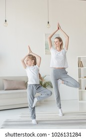 beautiful mother and daughter balancing in tree pose together