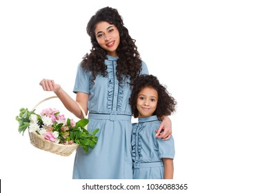 beautiful mother and daughter with basket of flowers isolated on white