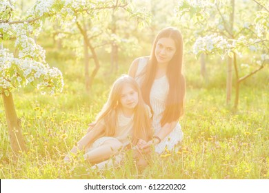 Beautiful mother and daughter in a blooming garden in the spring in the rays of the setting sun. Young mother tenderly hugs her daughter on nature in summer