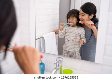 beautiful mother and daughter brushing teeth in the bathroom sink before going to bed