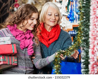 Beautiful mother and daughter buying Christmas decorations in store